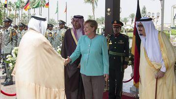 German Chancellor Angela Merkel (C) welcomed by Saudi Arabia's King Salman bin Abdulaziz Al Saud (R) before their official talks in Riyadh, Saudi Arabia