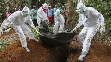 Liberian nurses bury the body of an Ebola victim on the outskirts of Monrovia, Liberia. (AP)