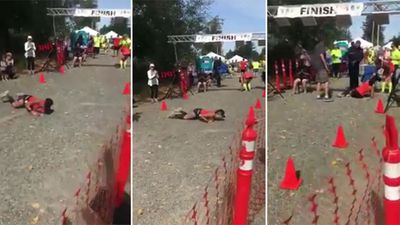 Determined marathon runner rolls over the finish line