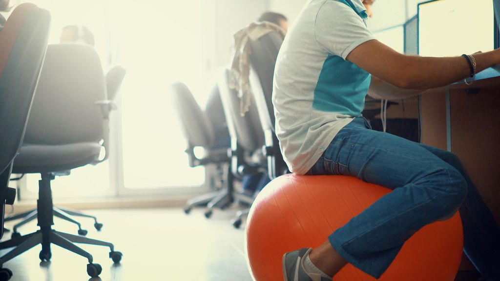 thinking of sitting on an exercise ball at work? here's why you