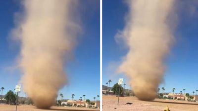 Huge dust devil hovers menacingly by side of road