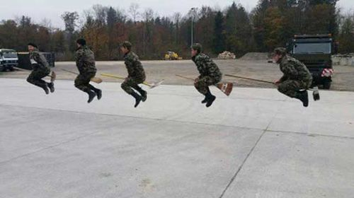 Photo of Swiss soldiers pretending to fly broomsticks.