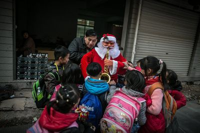 Children stroke a newly-made Santa Claus decoration held by a worker outside a factory.