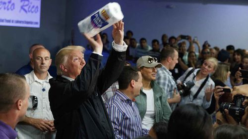 President Donald Trump tosses paper towels into the crowd during his visit to Puerto Rico in the aftermath of Hurricane Maria.