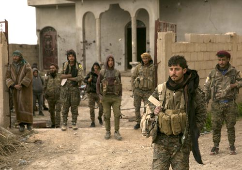 US-backed Syrian Democratic Forces fighters wait to go to the front line to oust Islamic State militants from Baghouz, Syria, in a photo dated March 14, 2019.