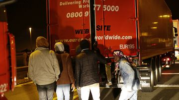 Migrants open a lorry in a failed attempt to cross the English Channel, in Calais. file photo (AAP)
