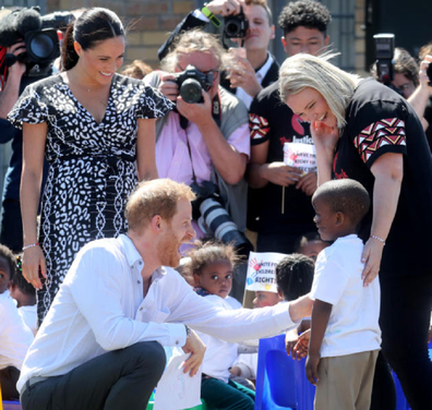 Prince Harry shares a laugh with a shy little boy in Nyanga.