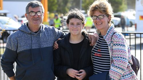 Mallacoota bushfire evacuees (L-R) Ron and Olivia and Lisa Short pose for a photo after arriving at the Somerville Recreation Centre in Somerville south-east of Melbourne, Saturday, January 4, 2019.