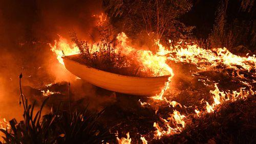 A bushfire spreads over a boat.