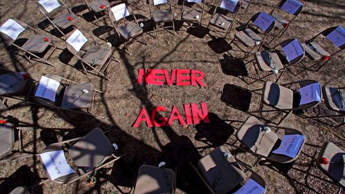 "Two rings of chairs encircle the words ""never again"" in a silent protest on this year's 19th anniversary of the Columbine High School shooting outside Trinity High School in Manchester, New Hampshire."