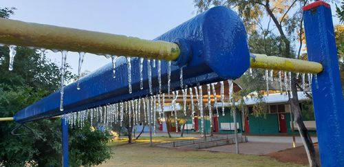 Play equipment at Ross Park Primary School had frozen tendrils due to the low overnight temperatures in the Top End.