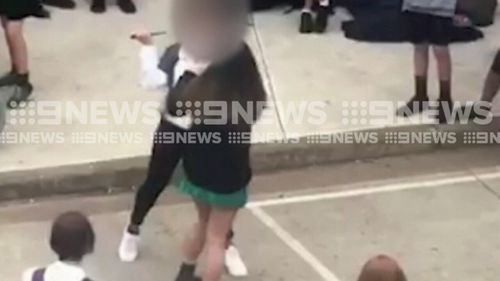The girl appears to draw the weapon to the face of the second girl. (9NEWS)