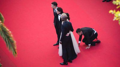 The intruder on his hands and knees on the Cannes red carpet. (Getty)