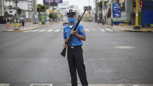 A Marine wearing a protective mask as a precaution against the spread of the new coronavirus stands guard to keep the streets cleared, in Lima, Peru.