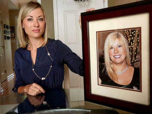 Kim Pack poses with a photo of her late mother, talk-show host April Kauffman. Picture: AP