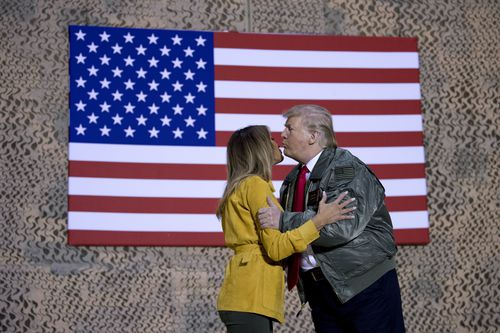 The Trumps exchange a kiss at the airbase in Iraq.