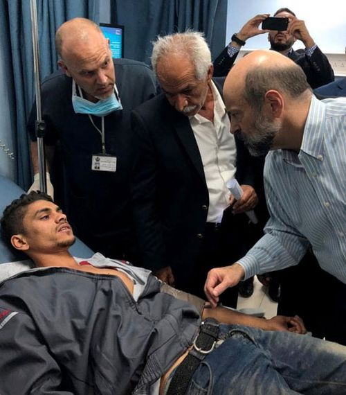 Jordan's Prime Minister Omar al-Razzaz, right, visits the injured flood victims in hospital.