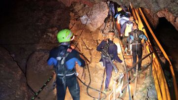 In this handout photo released by Thai Navy, Saturday, July 7, 2018, Thai rescue teams walk inside cave complex where 12 boys and their soccer coach went missing in Mae Sai, Chiang Rai province, northern Thailand. Chiang Rai Gov. Narongsak Osatanakorn says authorities are waiting for two big groups of volunteer divers to arrive later Saturday and Sunday, after which they'll be ready to begin the operation of bringing them out. (Thai Navy via AP)