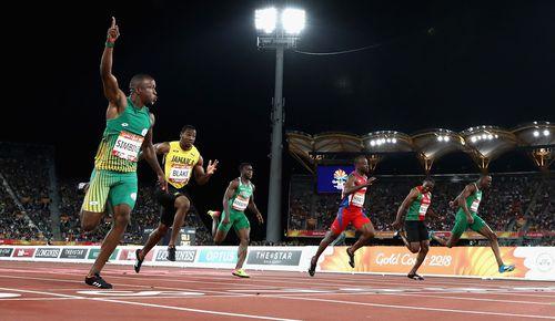 Akani Simbine crosses the finish line to win gold. (Getty)
