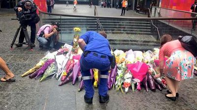 Members of the public lay bunches of flowers near the scene of the Lindt Cafe siege. (Twitter/@tiffgenders)