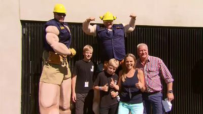Scott Cam poses for a photo with some Blockheads and some muscley Bizley construction workers. (9NEWS)