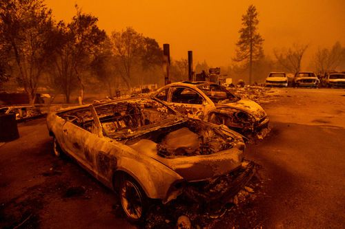 Scorched vehicles line a used car dealership after a wildfire burned through Paradise.