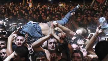 A fan who was dancing in the mosh pit at the Indio Solari show is lifted to remove him from the area, toward security. (AAP)