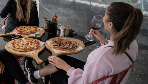 A group of women eating pizza and drinking wine at a restaurant in Bondi Beach, Sydney, Friday, May 15, 2020.