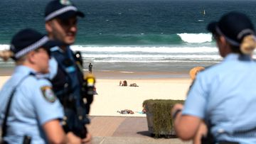 Police officers patrol Bondi Beach prior to its closure. Beachgoers drew condemnation yesterday when tens of thousands of people flouted social distancing rules, which have been put in place in an effort to limit the spread of COVID-19. Bondi Beach and other beaches have since been closed in Sydney's east.