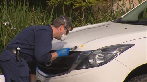 A police officer searches for evidence on a vehicle.