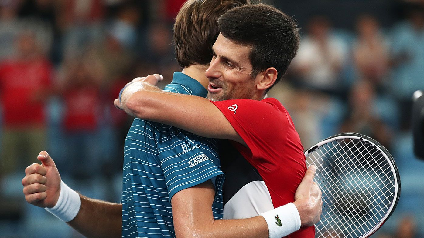 Novak Djokovic of Serbia and Daniil Medvedev of Russia come together after their semi-final