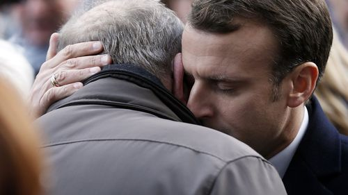 French President Emmanuel Macron embraces a grieving relative of the Bataclan terror attack.