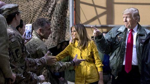 Donald Trump and first lady Melania Trump greet members of the military at a hangar rally at Al Asad Air Base, Iraq