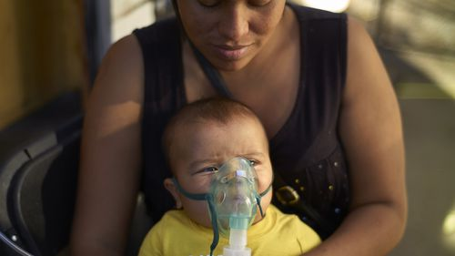 Honduran migrant Janet Zuniga holds her five-month-old son Linder, as he receives medical treatment outside a shelter, November 36 in Tijuana, Mexico.