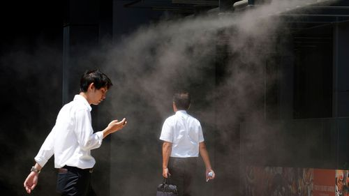 People cool down under a cooling mist spot at a building in Tokyo as temperatures soar above 35 degrees.