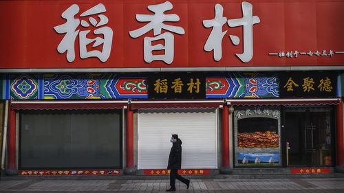 A Chinese man wears a protective mask as he walks by closed shops in a nearly empty commercial street in Beijing.