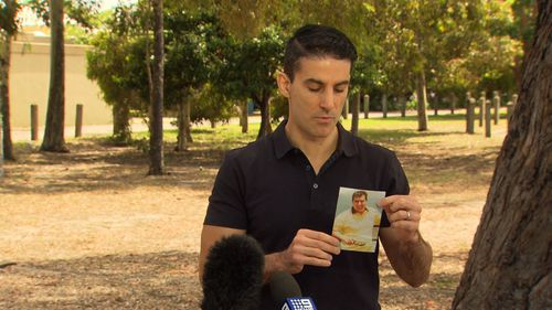 Mr Saristavros' son holds a picture of his murdered father during a press conference this morning.