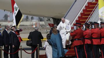 Pope Francis walks down the steps of an airplane as he arrives at Baghdad international airport, Iraq, Friday, March 5, 2021