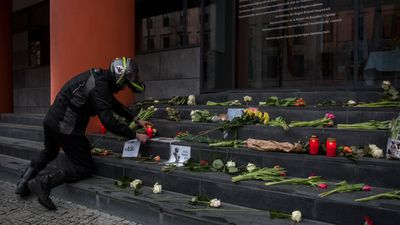 A man lights a candle at a tribute site outside the Belgium embassy in Berlin. (AFP)