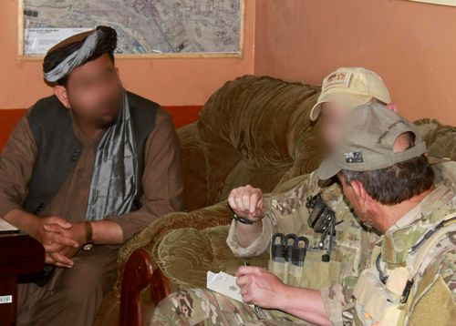 Former ADF soldier Shane Healey (middle) meets with a local Afghan on a 2012 mission in Uruzgan province.