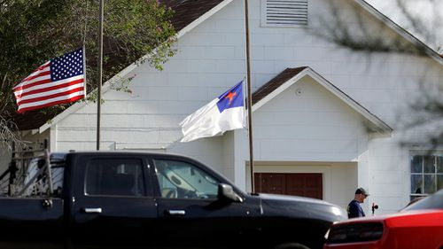 Flags fly at half-staff as law enforcement officials continue to investigate the scene of a shooting. (AAP)