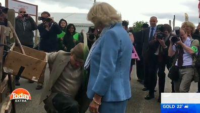 Camilla, Duchess of Cornwall pretends to knight a man using a leek