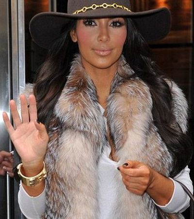 Kim Kardashian showing the tell-tale sign of a fake tan as she greets fans while leaving her New York hotel in 2013