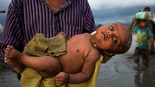 A Rohingya ethnic minority from Myanmar carries an infant past rice fields after crossing over to the Bangladesh side of the border near Cox's Bazar's Teknaf area. (AAP)