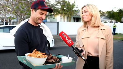 New Zealand Labour Party leader Jacinda Ardern's partner Clarke Gayford delivers home cooked food to the media waiting outside their house on October 17, 2020 in Auckland, New Zealand