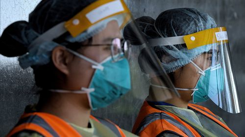 Health workers wearing full PPE wait for people to arrive for testing at a drive through coronavirus COVID-19 testing site in New South Wales.
