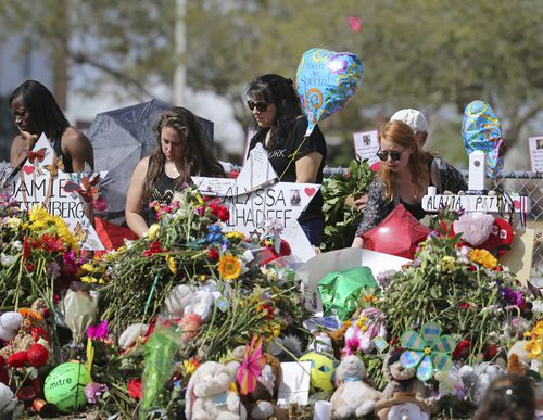 Mourners bring flowers as they pay tribute at a memorial for the victims of the shooting. (AAP)