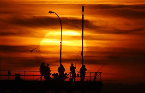 Fisherman take in a beautiful sunrise over Melbourne this morning before things heated up.