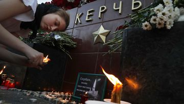 Candles are lit in a makeshift memorial outside Kerch Polytechnic College.