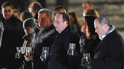French President Francois Hollande, third from right, holds a candle at Birkenau.